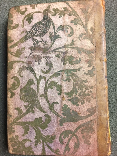 Brocade paper binding with gold birds and leaves on a red ground faded to pink